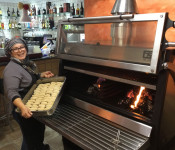 A Chef prepared to introduce a big tray of croquettes inside a PIRA 120 ED Charcoal Oven